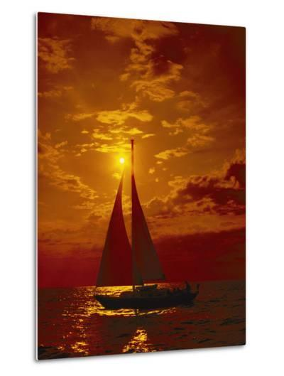 A Passing Sailboat is Silhouetted against a Brilliant Orange Sunset Near Bermuda-Todd Gipstein-Metal Print