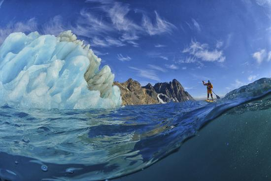 A Person Stand Up Paddle Boarding Near an Iceberg in the Fjords of Southeast Greenland-Keith Ladzinski-Photographic Print