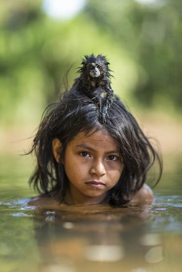 A Pet Saddleback Tamarin Hangs on Tight to a Matsigenka Girl as She Swims in the Yomibato River-Charlie Hamilton James-Photographic Print
