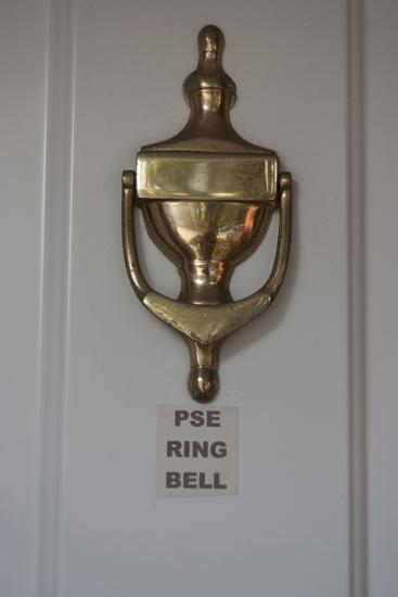 A Polished Brass Door Knocker, on a White Door of a Residential House-Natalie Tepper-Photo