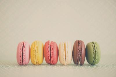 A Rainbow Selection of Sweet French Macarons Sitting in a Row.-Laura Evans-Photographic Print