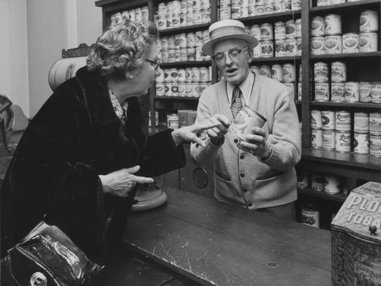 A Replica of an Early General Store Depicting a Salesman with a Can of Pears in Hand as He Tells a --Photographic Print