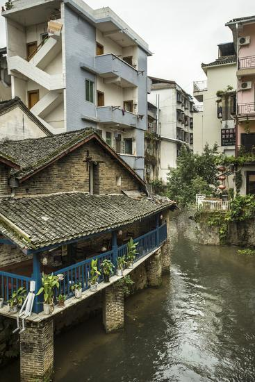 A Restaurant and Apartments Rise Above a River in Yangshuo, China-Jonathan Kingston-Photographic Print