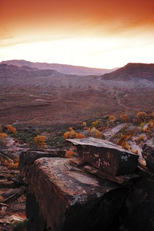 https://imgc.artprintimages.com/img/print/a-rock-covered-in-petroglyphs-in-a-desert-landscape-at-sunset_u-l-psw8uz0.jpg?p=0