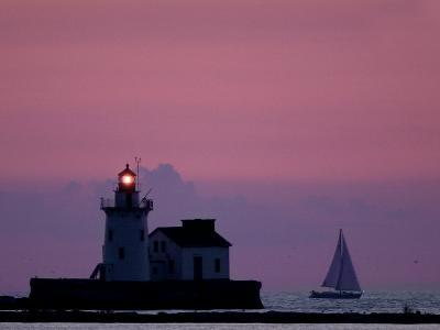 A Sailboat Slips Past a Lighthouse as the Sunset Comes to Lake Erie off the Coast of Cleveland--Photographic Print
