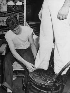 A Sailor in the Tailor Shop Aboard a US Navy Cruiser Checking Uniform Trousers of Another Sailor