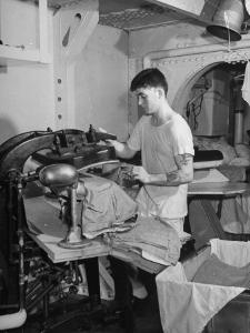 A Sailor Pressing Uniform Trousers in the Tailor Shop of a US Navy Cruiser