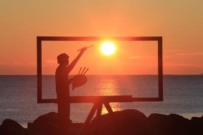 A Sculpture of an Artist Painting in New Castle, New Hampshire Frames the Sunrise-Robbie George-Photographic Print
