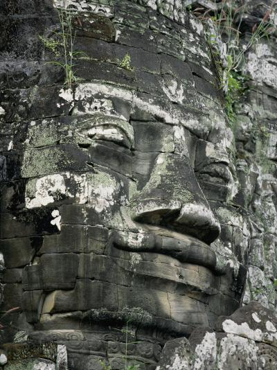 A Serene Likeness of Buddha Sculpted of Stone Peers from a Temple Wall-Paul Chesley-Photographic Print