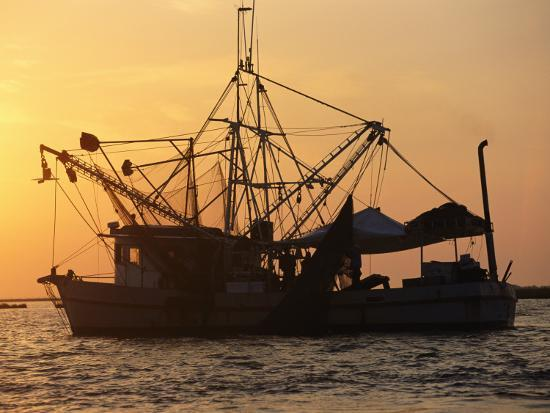 A Shrimp Boat Silhouetted against an Orange Sky--Photographic Print