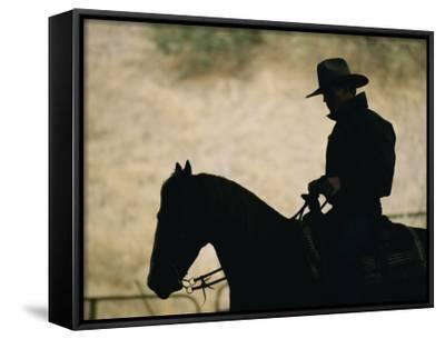 A Silhouette of a Rancher Riding a Horse-Dugald Bremner-Framed Canvas Print