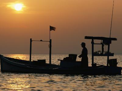 A Silhouetted Boat Fishing for Soft Crabs-Robert Madden-Photographic Print