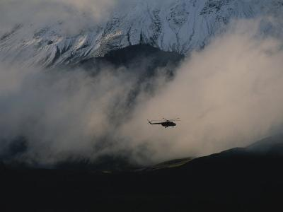 A Silhouetted Helicopter Flies over a Smoldering Crater-Peter Carsten-Photographic Print