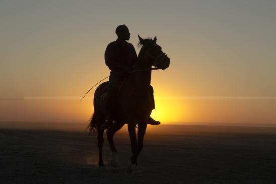 A Silhouetted Man on Horseback at Sunset-Beverly Joubert-Photographic Print