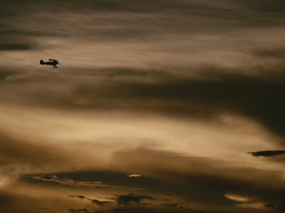 A Small Airplane Flies Through a Cloudy Sky over Key West, Florida-Raul Touzon-Photographic Print