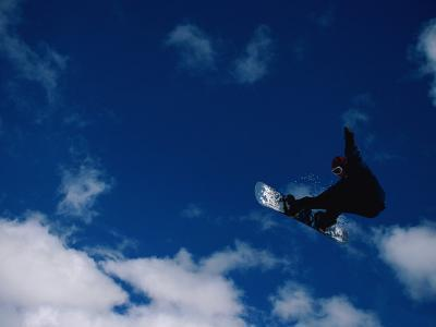 A Snowboarder Launches in the Air and Appears for a Second to Be Riding the Clouds-Barry Tessman-Photographic Print