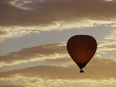 A Soaring Hot Air Balloon against a Cloud-Filled Sky at Dawn-Jason Edwards-Photographic Print