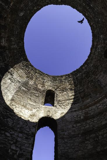 A Solitary Bird Flies Above an Opening in a Dome in Diocletian's Palace in Split-Jonathan Irish-Photographic Print