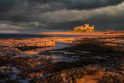 A Storm Passes Behind Bamburgh Castle with Last Light of Day Illuminating Rocky Shoreline-Garry Ridsdale-Photographic Print