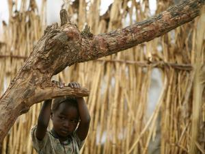 A Sudanese Girl Plays Inside a Thatched Hut at the Refugee Camp of Zamzam