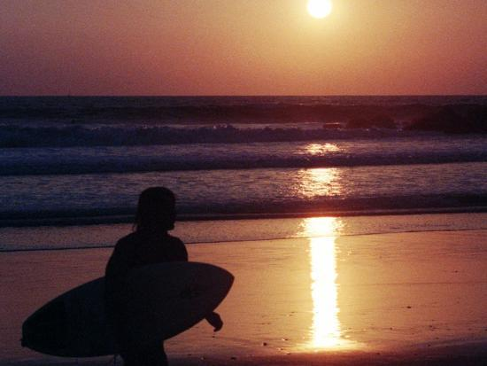 A Surfer is Silhouetted by the Setting Sun as He Leaves the Pacific Ocean on Venice Beach--Photographic Print