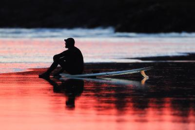 A Surfer Sits on His Surfboard While Watching the Waves at Sunset-Robbie George-Photographic Print