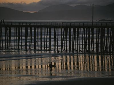 A Surfer Walks up the Beach Near a Pier at Twilight-Michael S^ Lewis-Photographic Print