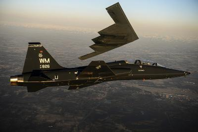 A T-38 Talon Flies in Formation with a B-2 Spirit--Photographic Print