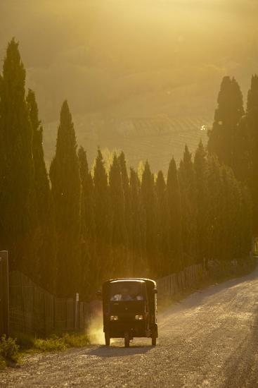 A Three Wheeled Van Drives Up a Dirt Road Lines with Cypress Trees-Tino Soriano-Photographic Print