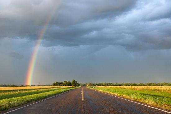 A Thunderstorm Produces a Vivid Rainbow Next to a Rain-Soaked Paved Road-Jim Reed-Photographic Print