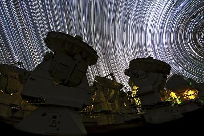A Time-Exposure Image of Star Trails over the Alma Radio Telescopes, 5000 Meters High in the Andes-Babak Tafreshi-Photographic Print