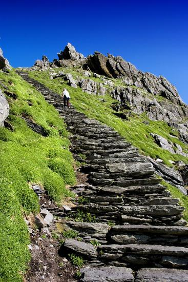 A Tourist Climbs Steps to Bee Hive Huts on Skellig Michael, County Kerry, Ireland-Chris Hill-Photographic Print
