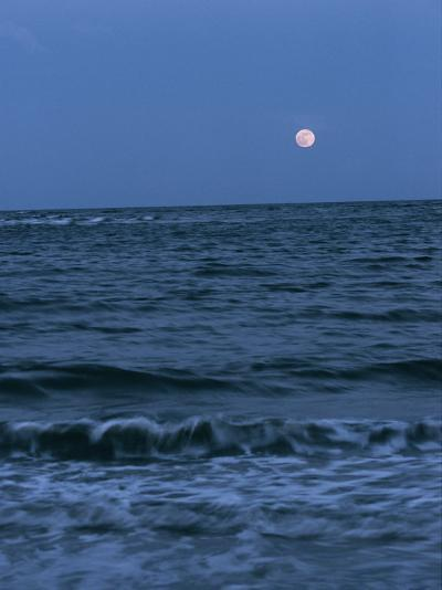 A Twilight Shot of Waves Coming into Shore with the Moon in the Background-Ira Block-Photographic Print