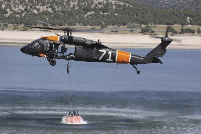 A U.S. Army Uh-60 Black Hawk Helicopter Collects Water from a Reservoir--Photographic Print