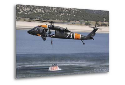 A U.S. Army Uh-60 Black Hawk Helicopter Collects Water from a Reservoir