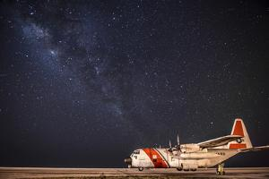 A U.S. Coast Guard C-130 Hercules Parked on the Tarmac on a Starry Night