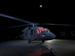 A UH-60 Black Hawk Helicopter Parked on the Flight Line under a Full Moon