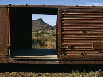 A View of a Distant Hill Through the Door of a Railway Car-Tim Laman-Photographic Print