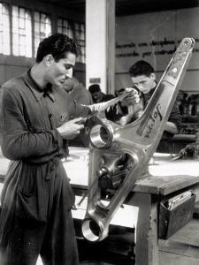 Technician Grinding a Piece of Metal Inside a Caproni Hangar by A. Villani