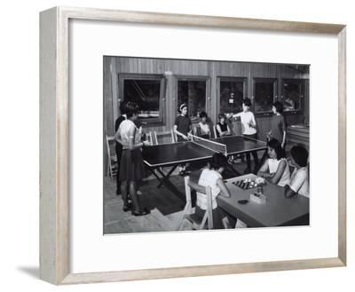 Two Girls Sitting at a Table are Playing Draughts, Four Young Woman are Playing Ping-Pong