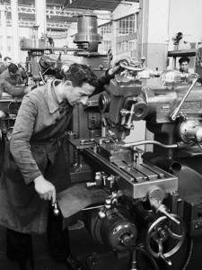 Worker Working at Various Machines in the Innocenti Automobile Factory by A. Villani