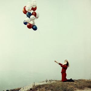 Young Woman in a Red Dress and Hat, Kneeling and Holding a Line with a Bunch of Colored Balloons by A. Villani