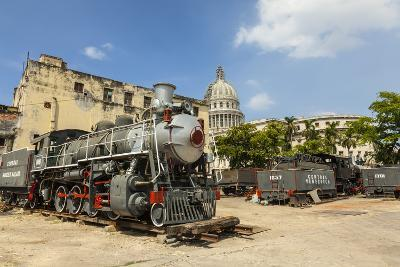 A Vintage Steam Train in a Restoration Yard with Dome of Former Parliament Building in Background-Sean Cooper-Photographic Print
