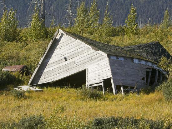 a weathered barn collapsed in alaska usa due to permafrost melt and