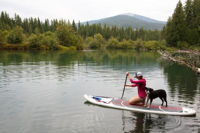 A Woman And Her Dog Shilo On Inflatable SUP Board At The Priest Lake Thoroughfare In North Idaho-Ben Herndon-Photographic Print