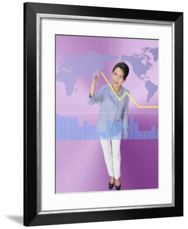 A Woman Drawing a Line Above a Bar Graph While Looknig at a World Map--Framed Photographic Print