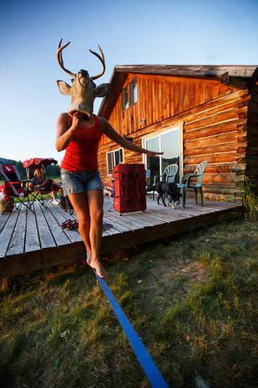 A Woman Holds A Mounted Deer Head While Walking A Static Line At Sunset In North Idaho-Ben Herndon-Photographic Print