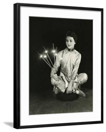 A Woman Holds Sparklers--Framed Photo