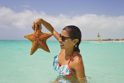 A Woman Holds Up a Starfish She Found in the Shallow Water Off of a Beach-Mike Theiss-Photographic Print
