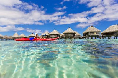 A Woman Kayaking in the Ocean at a Resort with Over-The-Water Bungalows-Mike Theiss-Photographic Print
